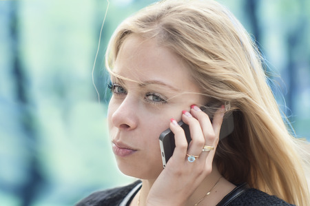 Portrait of a young serious woman talking on the mobile phone, outdoor blurred shot on blue background photo