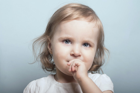 Nice portrait of a baby girl with the blue eyes  biting her finger, studio shot on blue. Stock Photo