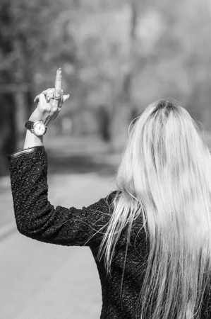 Young blonde woman walking away showing her middle finger. In black and white photo