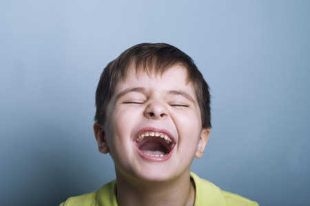 ultimately: Ultimately emotional portrait of a boy crying or laughing with mouth open and marks of chocolate oh his teeth. Studio horizontal shot