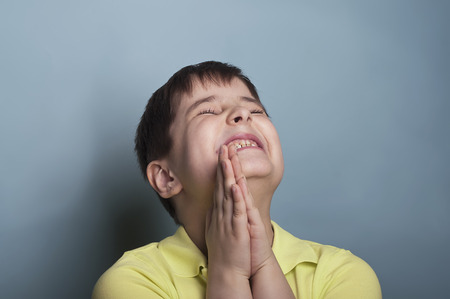 insist: Extremely emotional portrait of a boy of seven in stress, asking for something. Studio shot on blue Stock Photo
