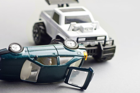 toy cars crashed, concept of a danger on a road. Studio shot on grey.