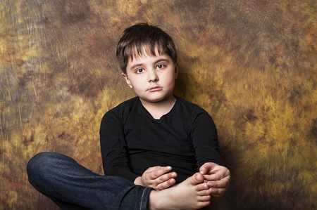 Portrait of a thoughtful boy posing with a bare foot in front photo