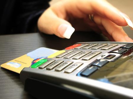 teclado num�rico: Primer plano de una tarjeta de cr�dito holding mano de la mujer sobre el terminal de pago