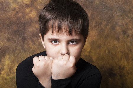 two faced: Little kid of seven, ready to fight, studio shot, Stock Photo