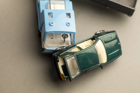 overhead shot: Plastic toy car tipped over and truck, concept of a danger of speed, overhead shot
