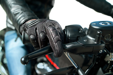 throttle: Closeup of the Hand of motorcyclist in protective glove on a throttle control, isolated on white