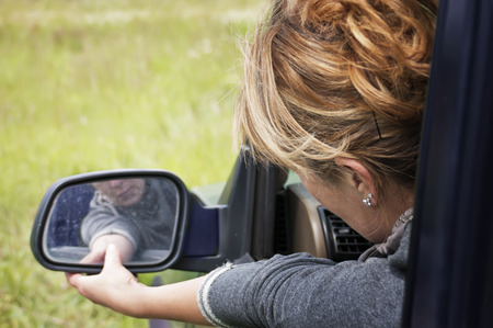 Female driver setting a side mirror of a car, outdoor shot, concept of safe driving