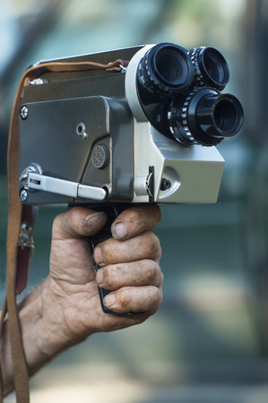 Old  unwashed hand holding retro film movie camera, focus on the hand, concept of hard job of filmmakers or journalists photo