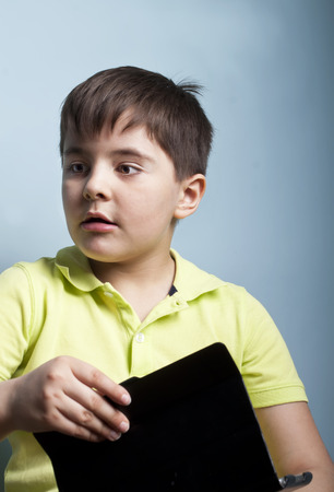 absent: Emotional portrait of a kid with an absent gaze, holding a tablet. Studio shot.