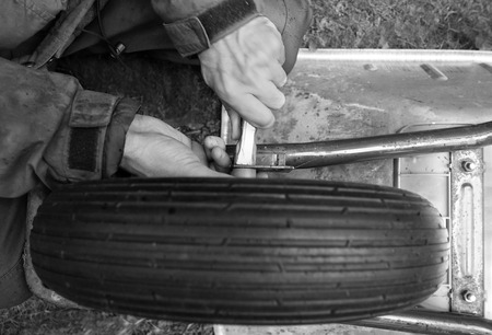Hands of mechanic tightening the nuts on a wheel of abstract mechanism, in black and white photo