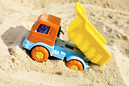 Toy tip lorry unloading sand, concept of construction photo
