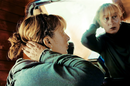 Side shot of a woman styling her hair in front of mirror, interior shot photo