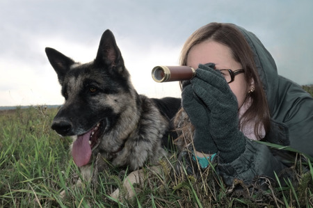 Woman with spyglass and dog waiting for the enemy, concept of conflicts photo