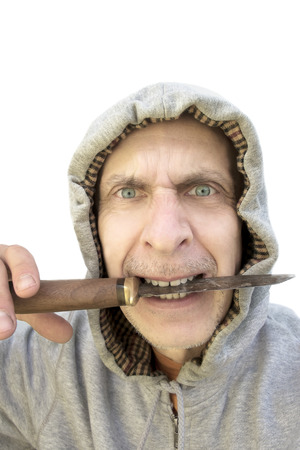 gritting: Aggressive Man in a hood holding knife in mouth, studio  portrait on white