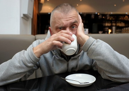 Matured man looking nervous having cup of espresso and looking straight into camera Reklamní fotografie