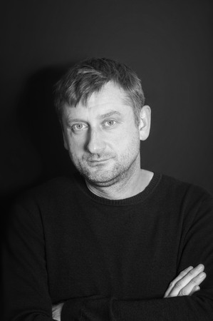 Mature man with arms crossed with a look of dejection in monochrome, vertical studio shot photo