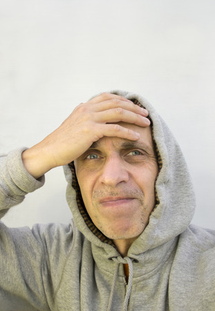 duh: What have I done - a man in a hood  slapping his forehead, vertical studio shot Stock Photo