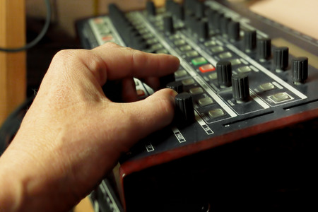Composer hand creating a tune on a digital synthesizer in his studio, indoor shot with selective focus photo