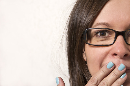 halitosis: Mod aged woman in glasses surprised, studio shot