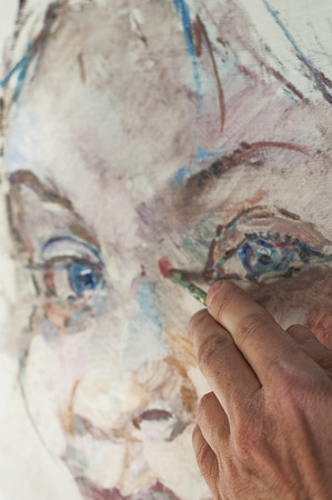Hand of artist at work, painting a female portrait, close up shot with particular focus