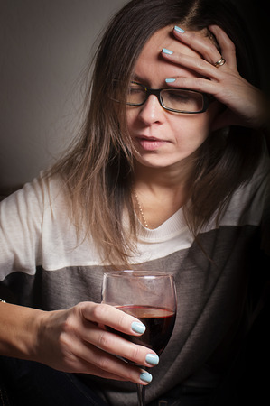 Drunk woman with half empty glass of wine having headache, indoor vertical shot with selective focus on glass Stock Photo