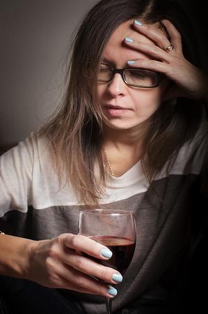 tomando alcohol: Mujer borracha con medio vaso vac�o de vino tiene dolor de cabeza, tiro vertical de interior con enfoque selectivo en vidrio