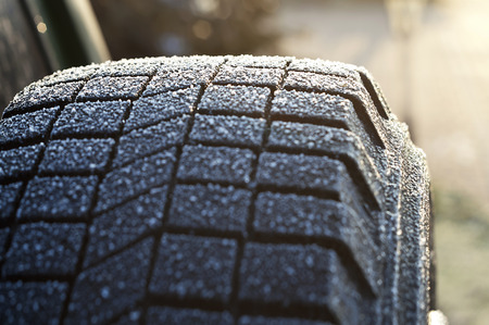 Close up of the ice and snowflakes on a spare tire, winter scene, concept of driving in bad weather photo