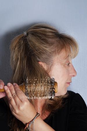 Woman combing her hair, vertical studio shot on blue