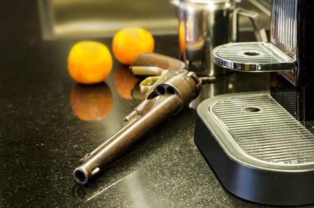 defensa personal: Todav�a la vida de un arma de la mano, m�quina de caf� y mandarinas en una mesa de la cocina, el concepto de defensa propia