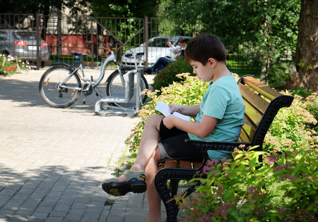 side shot: Side shot of a smart 7 years old boy reading a book in a park. Outdoors shot
