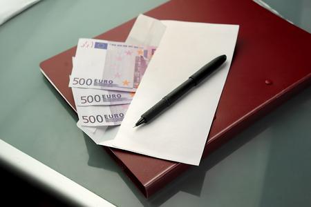 particolare: Busta aperta con tangente in euro, con penna e documenti in attesa di essere firmato. Colpo ambientale con particolare attenzione
