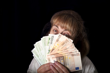 woman holding money: Portrait of a woman holding money in front of her face like a fan, spender concept