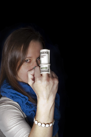 wag: Vertical shot of an angry woman flipping off with a roll of dollars on a middle finger