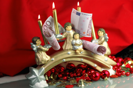 Christmas angles holding candles and 500 euro banknotes, indoor shot photo