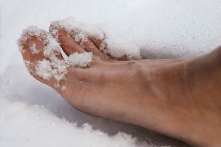 human foot: Close up of a human bare foot stuck the snow, outdoor shot with shallow depth of field