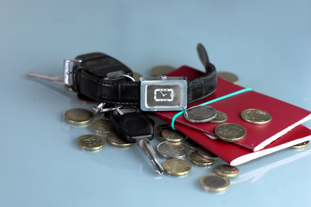 wrist watch: Still life of the wrist watch, coins and passports laid on a table, travel by car concept Stock Photo