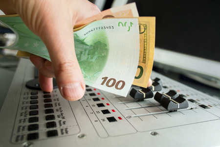 entertainment industry: Close up of DJ hand holding money and playing on mixing deck, concept of entertainment industry