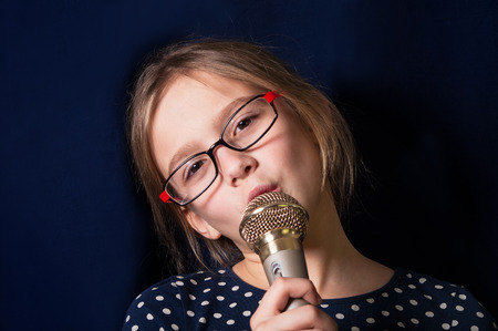 studio model: Portrait of a cute girl of ten making face and singing into microphone, studio shot on blue