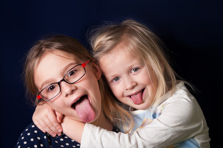 girl tongue: Two little girls making faces, studio horizontal shot Stock Photo