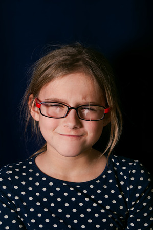 gaze: Portrait of a young girl with suspicious gaze, getting angry, studio vertical shot