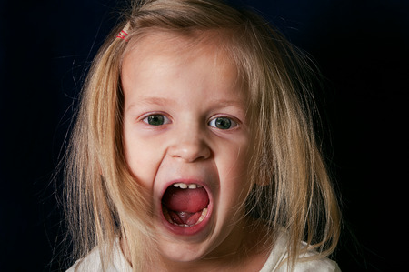 screaming face: Little girl screaming with open mouth, emotional horizontal studio shot