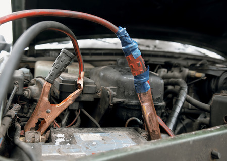 Close up of the old  jump leads wrapped by tape on a car flatten battery, outdoor shot with particular focus Stock Photo - 35595655