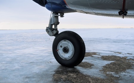 light duty: Close up of a plane landing gear, endless snowfield in thr background, outdoor shot with selective focus