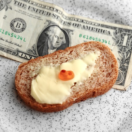 pitiful: Close up overhead shot of pitiful amount of red caviar on a top of bread with butter, dollar banknote in the background Stock Photo