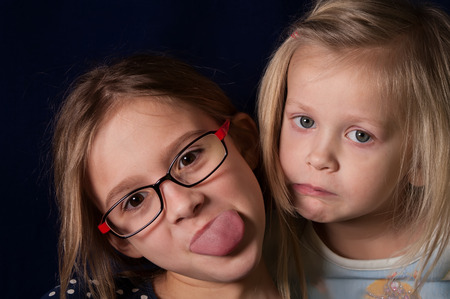 10 years girls: Two little girls making faces, studio horizontal shot Stock Photo