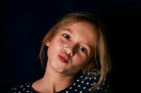 making face: Studio shot of a beutiful teenage girl, making face