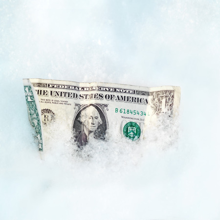 Close up of a crumpled dollar bill in a snow, business concept photo