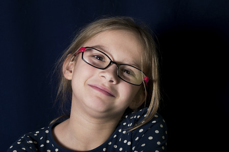 tilted: Portrait of a beautiful young girl wearing glasses with tilted head, studio shot