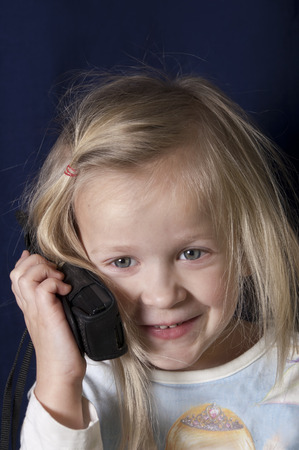 messy hair: Little cute girl with messy hair on a retro mobile phone, studio vertical shot